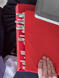 © Licensed to London News Pictures. 06/12/2017. London, UK. Brexit Secretary David Davis leaves his office in Downing Street carrying his red ministerial folder (here image rotated 180 degrees) shows tabs with subject headings. Mr Davis is answering questions from fellow MPs at the Commons Brexit Committe in Parliament right now. Photo credit: Peter Macdiarmid/LNP