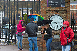 © Licensed to London News Pictures. 30/04/2018. London, UK. People with umbrellas at the Royal Observatory in  Greenwich Park in London during wet and windy weather. The capital has been experiencing heavy rain and windy weather today. Photo credit: Vickie Flores/LNP