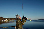 Kevin Rexford reels in a Perch while fishing on the Seneca Lake Pier in Watkins Glen, NY, Friday, Nov. 14, 2014.<br /> (Heather Ainsworth for The New York Times)