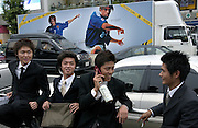 Four young, very cool, Japanese men hang out outside Harajuku Station as a mobile truck drives past advertising the 2002 World Cup. Harajuku is the trendiest area in Tokyo, where every Sunday locals come out dressed to impress. Japan 23/06/02..©David Dare Parker/AsiaWorks Photography