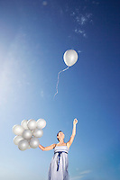 Woman holding balloons against sky one flying away low angle view