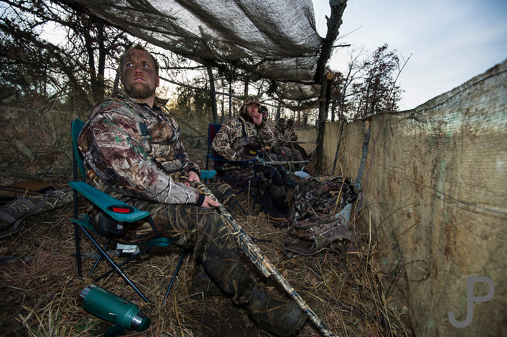 Gary Friend (foreground) looks for incoming ducks while hunting on a private watershed lake in Shamrock, Oklahoma