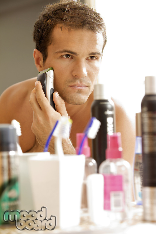Reflection of young man in mirror shaving with electric shaver