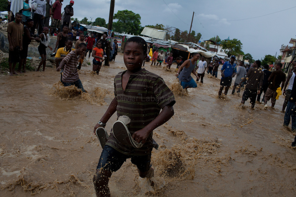 After hurricane Tomas went through Haiti, the city of Leogane has been totally flooded by the heavy rain and the overflow of the river Roullorne.///Haitians walk in the muddy water, in a street of Leogane during hurricane Tomas.
