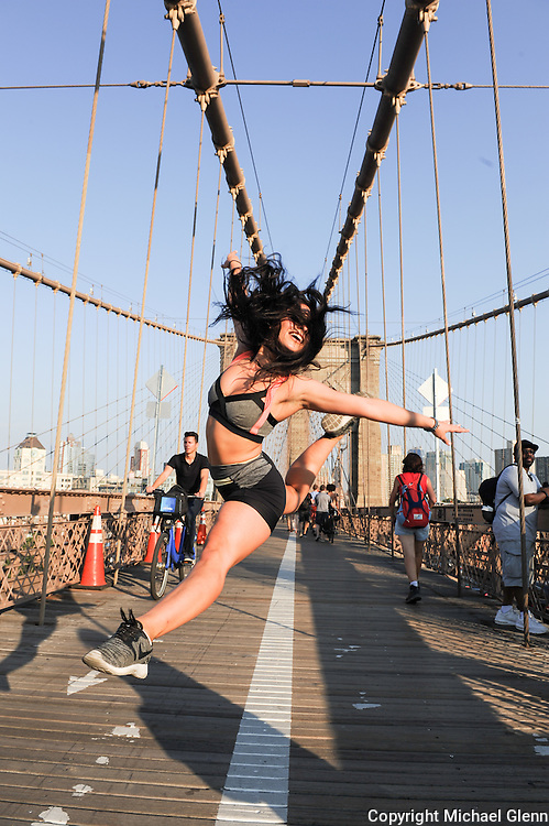 Mari does a split jump on the pedestrian walkway of the Brooklyn Bridge