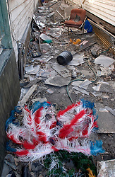 25 Oct,  2005.New Orleans, Louisiana. Hurricane Katrina aftermath.<br /> The 8th ward lies in ruins following Katrina's devastating floods. A mardi gras indian's headress lies in the dirt between two houses. <br /> Photo; &copy;Charlie Varley/varleypix.com