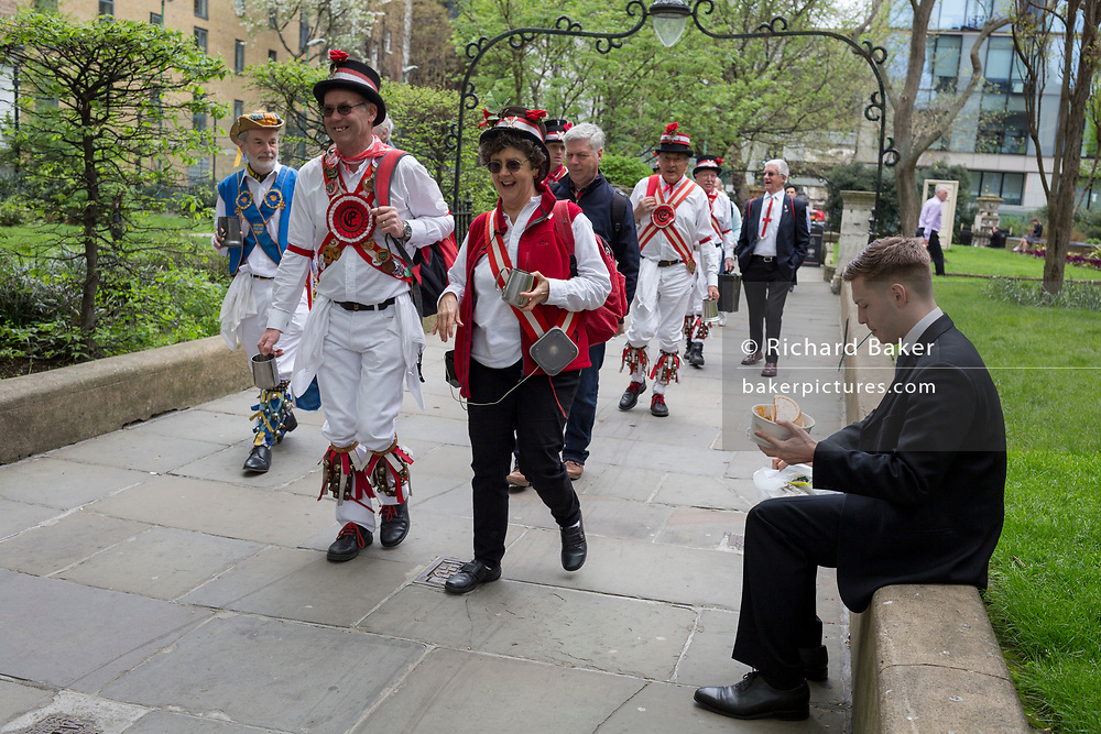 Morris Men walk past a young City worker at lunchtime on St George's Day in the gardens of St Botolph's without Bishopsgate church in the capital's financial district (aka The Square Mile), on 23rd April, City of London, England.