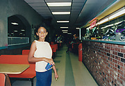 A girl standing in the food area of a rollerblading centre, USA