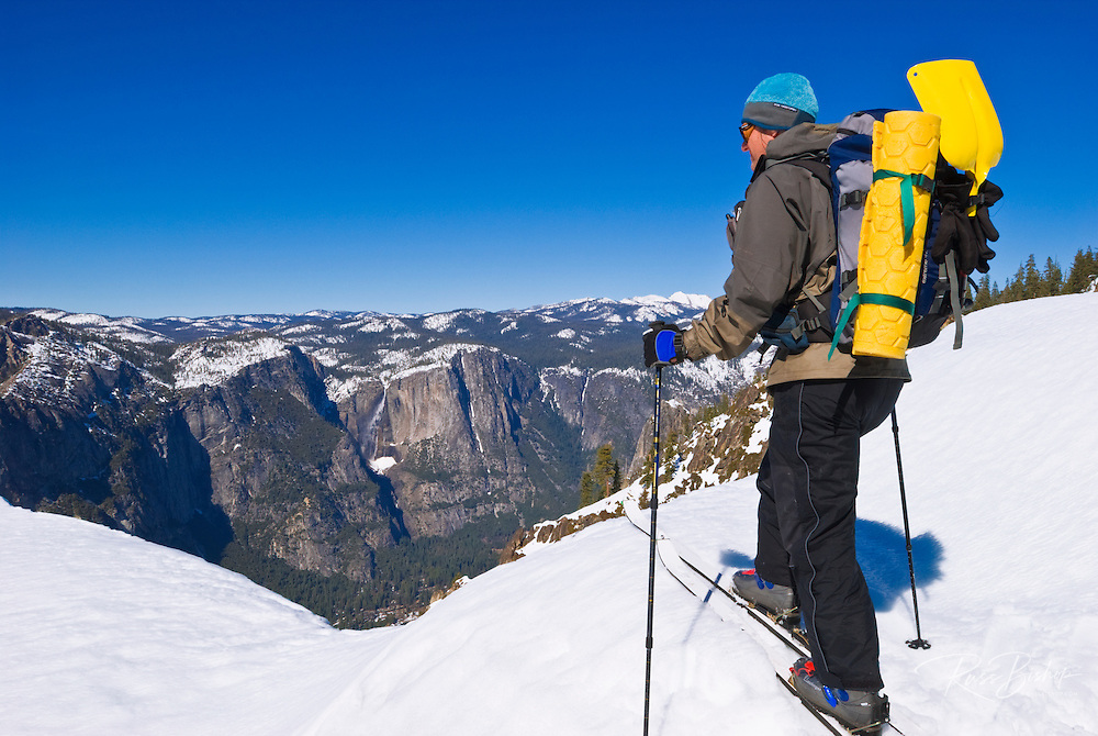 Backcountry skier looking down on Yosemite Falls from Taft Point in winter, Yosemite National Park, California