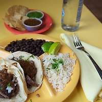 A plate of beef tacos with rice, beans, chips, and salsa at Bumble Bee's Baja Grill.