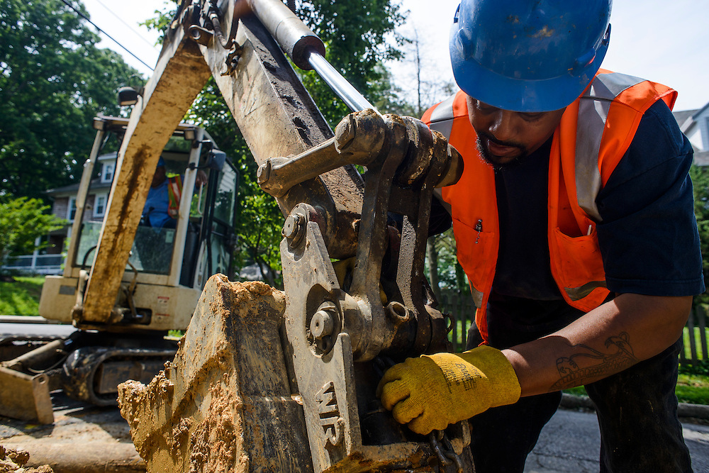 Photo by Matt Roth<br /> <br /> Baltimore City Department of Public Works laborer Charles Lee, fastens a new fire hydrant to Stanley Maith's back hoe at the intersection of Tyndale Ave., and Canfield Ave. in Baltimore, Maryland on Wednesday, May 29, 2013.