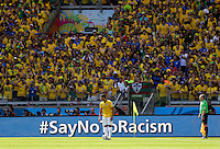 Hulk of Brazil stands in front of Brazil fans and a sign saying - Say not to Racism