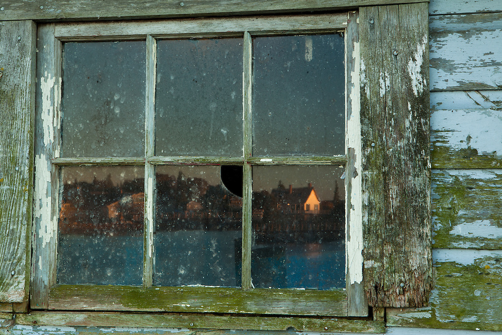 late day light reflects a quaint fishing village in a weathered and brocken window, bass harbor, Maine