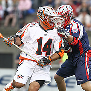 Justin Pennington #14 of the Denver Outlaws tries to get past Paul Rabil #99 of the Boston Cannons during the game at Harvard Stadium on May 10, 2014 in Boston, Massachusetts. (Photo by Elan Kawesch)