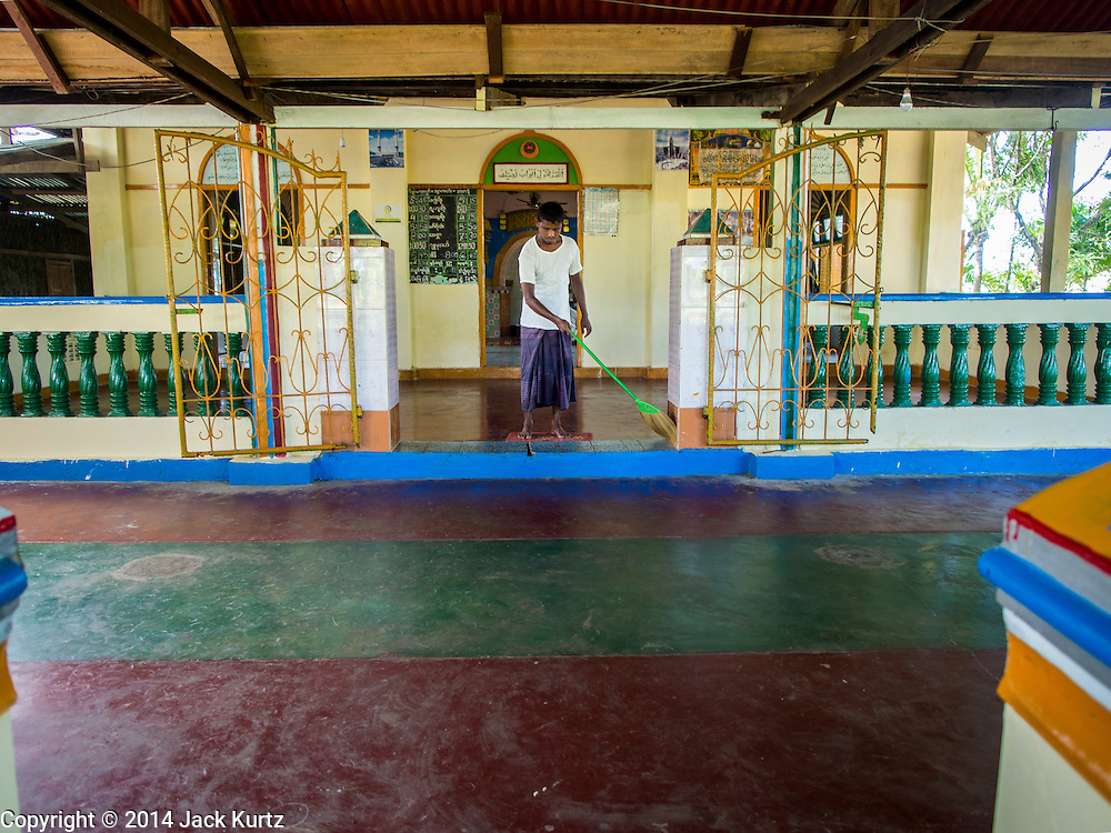 06 NOVEMBER 2014 - SITTWE, RAKHINE, MYANMAR: A caretaker cleans a mosque in a Rohingya Muslim IDP camp near Sittwe. After sectarian violence devastated Rohingya communities and left hundreds of Rohingya dead in 2012, the government of Myanmar forced more than 140,000 Rohingya Muslims who used to live in and around Sittwe, Myanmar, into squalid Internal Displaced Persons camps. The government says the Rohingya are not Burmese citizens, that they are illegal immigrants from Bangladesh. The Bangladesh government says the Rohingya are Burmese and the Rohingya insist that they have lived in Burma for generations. The camps are about 20 minutes from Sittwe but the Rohingya who live in the camps are not allowed to leave without government permission. They are not allowed to work outside the camps, they are not allowed to go to Sittwe to use the hospital, go to school or do business. The camps have no electricity. Water is delivered through community wells. There are small schools funded by NOGs in the camps and a few private clinics but medical care is costly and not reliable.   PHOTO BY JACK KURTZ