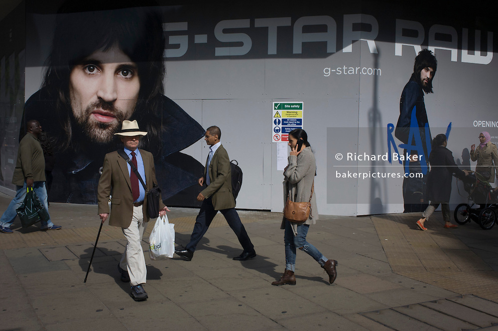 Pedestrians pass-by a large hoarding ad for an opening store of G-Star on London's Oxford Street.