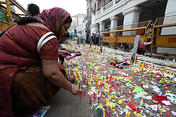 © Licensed to London News Pictures. 13/11/2012. Delhi, India. A woman lights candles and lamps (known as Dipa), which signifies the triumph of good over evil, outside the Shish Ganj Gurudwara Sikh Temple in Delhi, during the first day of Diwali. Photo credit : Richard Isaac/LNP