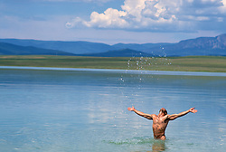 naked man in a lake splashing water in the air