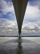 the Pont de Normandie near to Honfleur in Normandy, France. The Pont de Normandie (or Bridge of Normandy) is a cable-stayed road bridge that spans the river Seine linking Le Havre to Honfleur in Normandy, northern France. Its total length is 2143.21 m (856 m between the 2 piers). The bridge was designed by Michel Virlogeux. The architects were François Doyelle and Charles Lavigne.[1] Construction by Bouygues, Campenon Bernard, Dumez, Monberg & Thorson, Quillery, Sogea and Spie Batignolles[1] began in 1988 and lasted 7 years. The bridge opened on January 20, 1995.  At that time the bridge was both the longest cable-stayed bridge in the world, and had the record for the longest distance between piers for any cable-stayed bridge. It was more than 250 m longer between piers than the previous record. This record was lost in 1999 to the Tatara Bridge in Japan. Its record for length for a cable-stayed bridge was lost in 2004 to the 2883 meters of the Rio-Antirrio. At the end of construction, the bridge had cost $465 million.  The cable-stayed design was chosen because it was both cheaper and more resistant to high winds than a suspension bridge. [from Wikipedia]