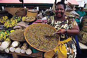 Prossy Kasule in stall no. 68 of the Nakasero Market offer roasted and salted grasshoppers for sale, Kampala, Uganda. (Man Eating Bugs page 148 Bottom)