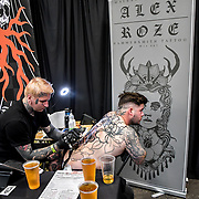 Alex Roze tattoo a client at The Great British Tattoo Show, London, UK