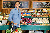 Handsome young man holding basket at vegetable stall in supermarket