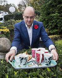 © Licensed to London News Pictures. 09/11/2017. Whitam, UK. Alex Sawyer, husband of Priti Patel, brings out a tray of tea and cake for reporters waiting outside their house. Priti Patel resigned from government yesterday. Photo credit: Peter Macdiarmid/LNP