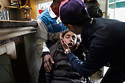 A girl affected by teargas is rescued in a café during a manifestation. People demonstrate in the street of Tunis asking for the party of ousted president Ben Ali (RCD) step down immediately despite the new national unity governement announced election in 60 days.