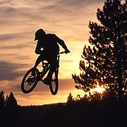 A photo of a man jumping his bike while mountain biking at sunset near Truckee, CA.