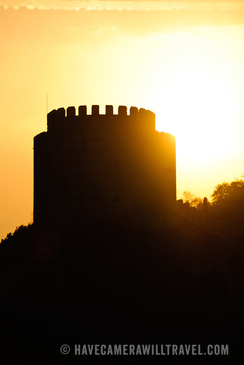 Silhouette against the setting sun of the Rumelian Castle (Rumelihisari), a 15th century fortress on the banks of the Bosphorus in Istanbul, Turkey.