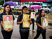 04 OCTOBER 2017 - CHONBURI, CHONBURI, THAILAND: Mourners carry portraits of Bhumibol Adulyadej, the King of Thailand, in the parade before the races. Contestants race water buffalo about 100 meters down a muddy straight away. The buffalo races in Chonburi first took place in 1912 for Thai King Rama VI. Now the races have evolved into a festival that marks the end of Buddhist Lent and is held on the first full moon of the 11th lunar month (either October or November). Thousands of people come to Chonburi, about 90 minutes from Bangkok, for the races and carnival midway.   PHOTO BY JACK KURTZ