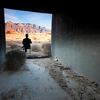 man sitting in  chair at the threshold of the manmade and the nautral landscape, conjuring notions of environmental contrast.taken near the sandia mountains of albuquerque, new mexico.