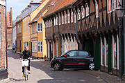 Locals and small saloon car in medieval street in Ribe centre, South Jutland, Denmark