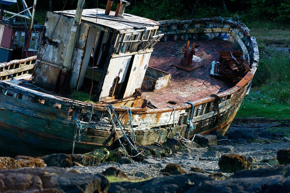 Isle of Mull, Inner Hebrides, Scotland. Abandoned inshore fishing boat decaying on the shore at Salen