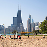 People playing volleyball at North Avenue Beach with the Chicago skyline and John Hancock building in the background.