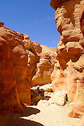 The river bed is created by flash floods that are common in the area of Timna natural and historic park, Israel, The Timna Valley is located in the southwestern Arava, some 30 km. north of the Gulf of Eilat. The traces of ancient civilizations are, too, very interesting to look at in Timna. Copper mining was known there at least from the 18th century B.C. Later Egyptians, who conquered the area, made Timna a very important source of copper. There are many ancient copper mines in the valley, some look like holes in the ground, others are caves hewn in stone; in some places, there are remains of copper-smelting ovens. There is a place where you can see Egyptian rock drawings. At the foot of Solomon's pillars there are remains of an Egyptian temple, and above them are two figures, one of them a pharaoh, engraved in stone by Egyptians.
