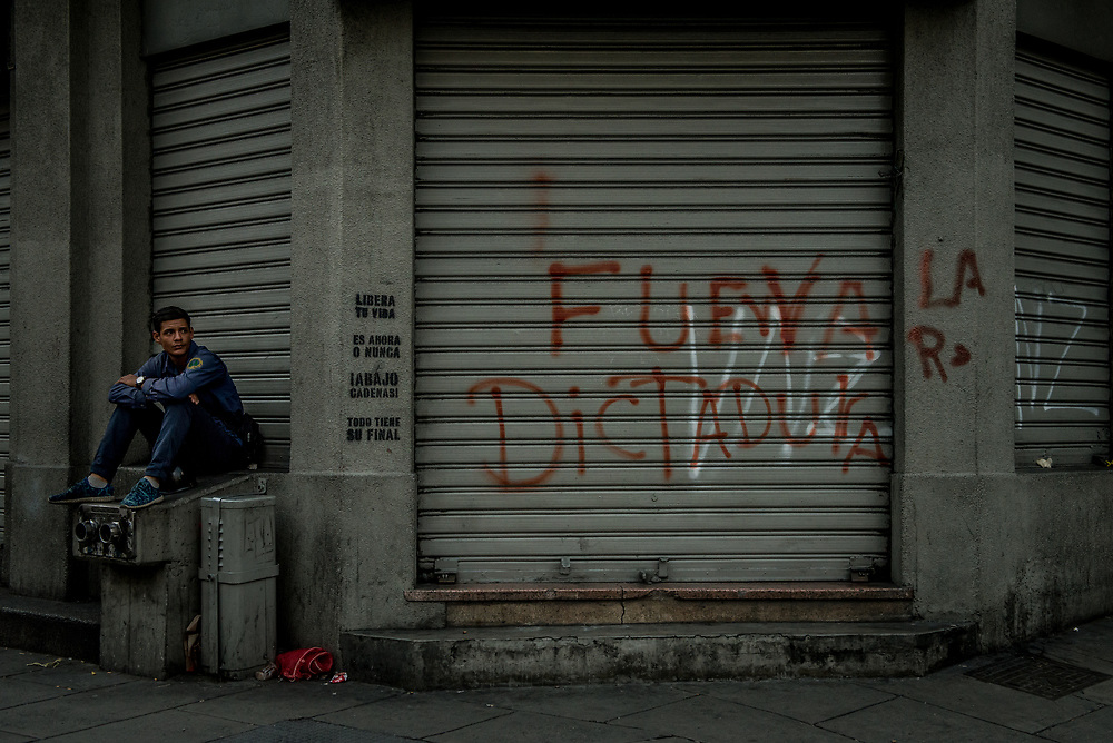 "CARACAS, VENEZUELA - JULY 27, 2017: A man sits next to a shop closed in support of a national strike, with graffiti on the security door that says, in Spanish: ""Go Away Dictatorship"". The political opposition called for a 48 hour national strike for July 26th and 27th, and for their supporters to close businesses, not go to work, and instead create barricades to block off their streets.  Opposition controlled areas of the country were completely shut down.  The strike was called as part of the opposition's civil resistance movement - that began on April 1st, to protest against the Socialist government's attempt to elect a new constituent assembly that will have the power to re-write the constitution, and will threaten democracy.  PHOTO: Meridith Kohut for The New York Times"