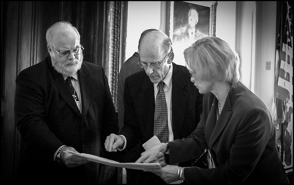 Sen. Pat Roberts looks over the floor plan of the Hart Building with Incident Commander David Stutz and Secretary of the Senate Jeri Tompson, while on the right Greg Martin, Doctor of Infecteous Diseses at Bethesda Naval Hospital answers questions from Sen. Brownback after a meeting in Senator Daschle's office concerning the reopening of the Hart Building. 10/24/01..©PF BENTLEY/PFPIX.com