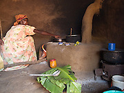 Inside a kitchen using a fuel efficient stove. This is one of the many skills learnt in a Send a Cow group. The stove burns much less fuel and the smoke leaves the room through the chimney, making it a much healthier stove to cook on.