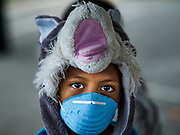 """22 JANUARY 2018 - GUINOBATAN, ALBAY, PHILIPPINES: A boy in an evacuation center in Guinobatan wears a face mask. Several communities in Guinobatan were hit ash falls from the eruptions of the Mayon volcano and many people wore face masks to protect themselves from the ash. There were a series of eruptions on the Mayon volcano near Legazpi Monday. The eruptions started Sunday night and continued through the day. At about midday the volcano sent a plume of ash and smoke towering over Camalig, the largest municipality near the volcano. The Philippine Institute of Volcanology and Seismology (PHIVOLCS) extended the six kilometer danger zone to eight kilometers and raised the alert level from three to four. This is the first time the alert level has been at four since 2009. A level four alert means a """"Hazardous Eruption is Imminent"""" and there is """"intense unrest"""" in the volcano. The Mayon volcano is the most active volcano in the Philippines. Sunday and Monday's eruptions caused ash falls in several communities but there were no known injuries.    PHOTO BY JACK KURTZ"""