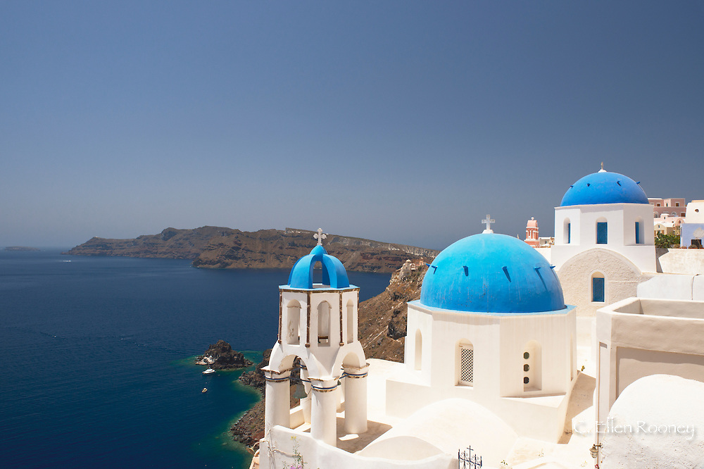 Blue domed Greek Orhtodox churches overlooking the caldera in Oia, Santorini, The Cyclades, The Aegean, The Greek Islands, Greece, Europe