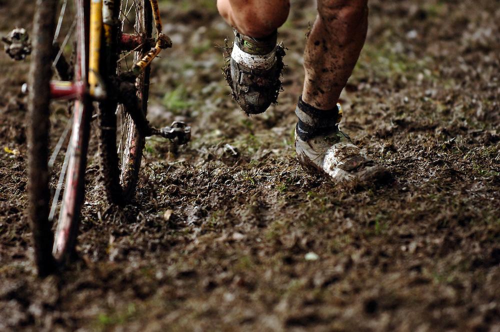 DETROIT, MICHIGAN - USA -  A cyclocross bike racer runs up a muddy, slippery hill.(Photo by Bryan Mitchell)