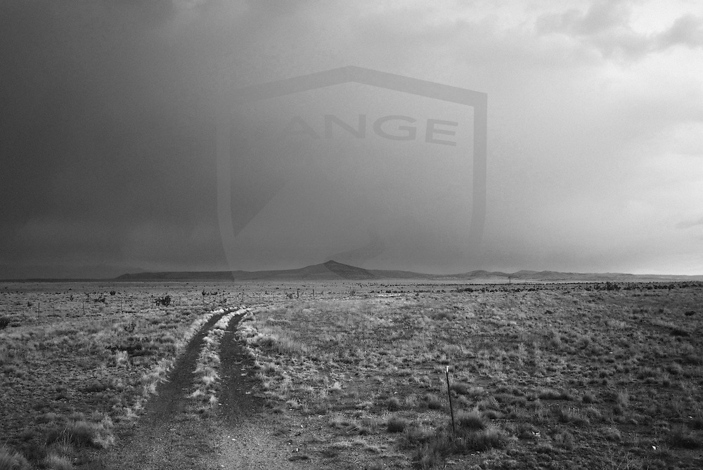 a country dirt road leads into the distance near santa fe, new mexico.  black and white.