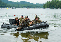 "The Navy Seal Team with their K-9 Raven charge the beach during their mission demonstration at Wellington State Beach on Newfound Lake following the ""Swim With a Mission"" event Friday afternoon.  (Karen Bobotas/for the Laconia Daily Sun)"