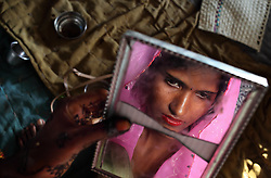 Radha, 15, observes herself in a cracked mirrorvthe day before her wedding. Despite legislation forbidding child marriage in India (Child Marriage Restraint Act-1929), the much more progressive Prohibition of Child<br />