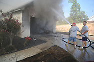 Lafayette County firemen, Oxford firemen, and volunteers extinguish a house fire at 111 Eastwind Drive off of Highway 30 in Oxford, Miss. on Friday, September 17, 2010.