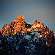 The first rays of light from sunrise bathe Grand Teton in orange light in late autumn near Jackson, Wyoming.
