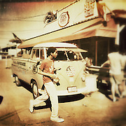 A boy walks past a vintage VW Camper on the north shore of Maui, USA