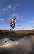 Mountain biker, BMXer, James Hitchcox, in full protection getting some air on the track, UK, 2000's