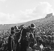 Women being helped over the railing by spectators and guards at the All Ireland Senior Gaelic Football Final Down v. Offaly in Croke Park on the 24th September 1961.